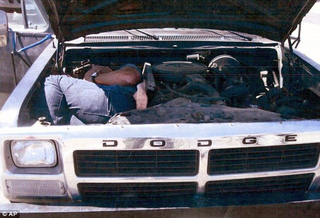 Tight squeeze: Customs officers caught this illegal immigrant trying to smuggle himself into the U.S. in the engine compartment of a pick-up truck