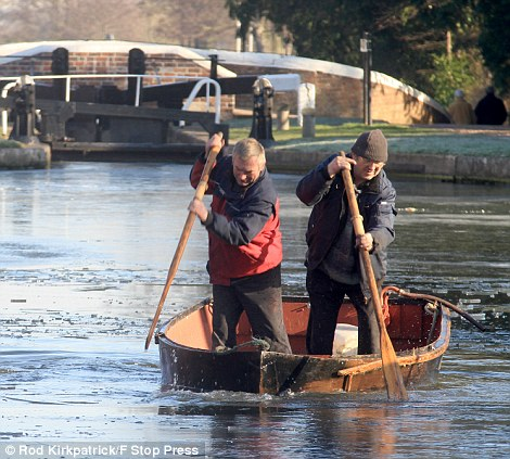 Frozen: Marine Engineers, Andy Poacher and Graham Donohue, use oars and a rowing boat to break up ice at Fradley Junction near Lichfield, Staffordshire
