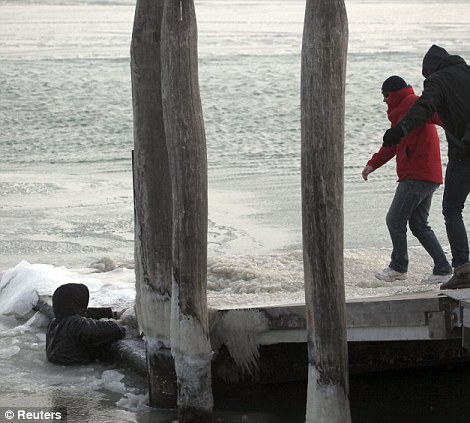 A passerby helps rescue a man after he had fallen into a partially frozen lagoon in Venice