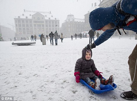 A man pulls his child on a sled at the Dam in Amsterdam