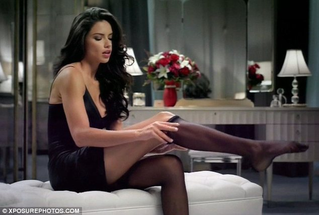 Inside her boudoir: Adriana Lima was seen getting ready for a hot date as she slipped on some suspenders in her first Super Bowl commercial for Teleflora