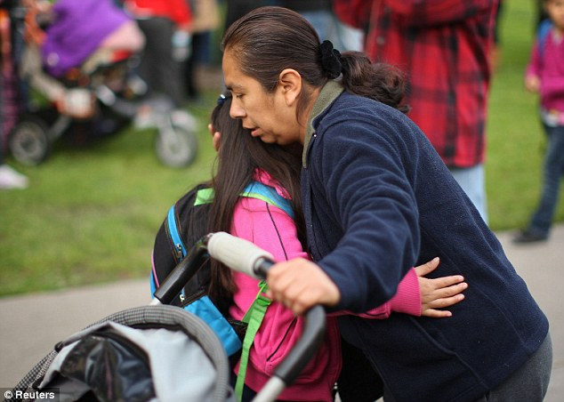 Comforting: A parent hugs her child at the start of the school day. School bosses say they are trying to 'govern emotion' as the investigation continues