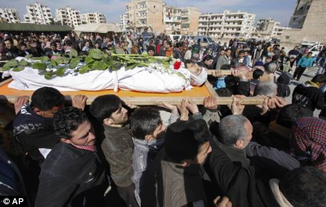 Massacre: Mourners carry the body of a Syrian rebel killed by government forces. More than 5,400 people were killed in Syria between March and December last year, according to UN figures
