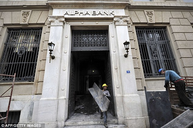 De limpieza: Los trabajadores retirar los escombros de la sede del Banco Alfa en la secuela de disturbios generalizados en Atenas el domingo por la noche