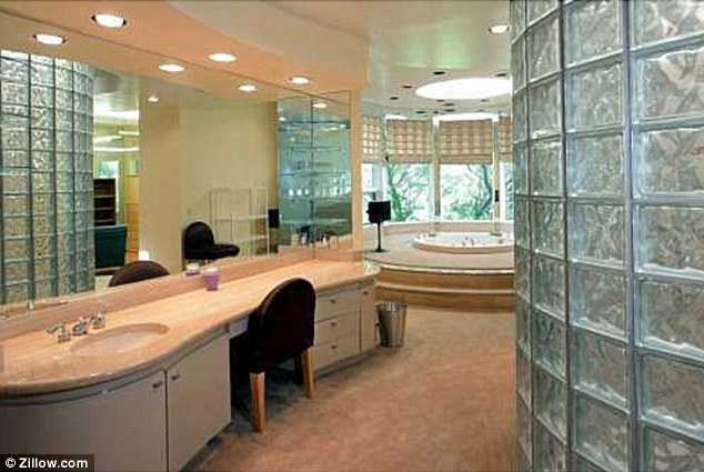 Beige decor: The bathroom is kitted out with neutral fixtures and fittings, with the addition of glass bricks in the wall space