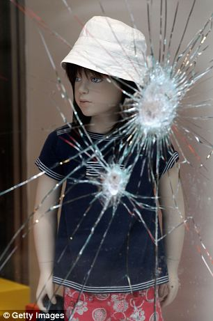 A mannequin of a child stands behind the damaged window of a fashion store in the centre of the capital
