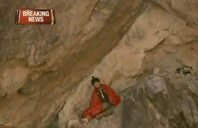 Rescue: The daredevil looks out sheepishly as he sits on the narrow ledge awaiting rescue