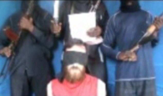 Video plea: One of the hostages, believed to be Chris McManus, is seen pleading for his life as his armed captors stand behind him in the second video to be released by his kidnappers in December