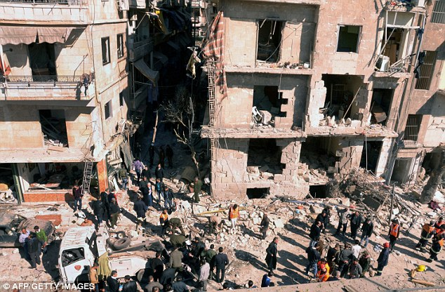 Investigators inspect the blast scene outside a damaged building following a car bomb in Syria's second largest city of Aleppo l
