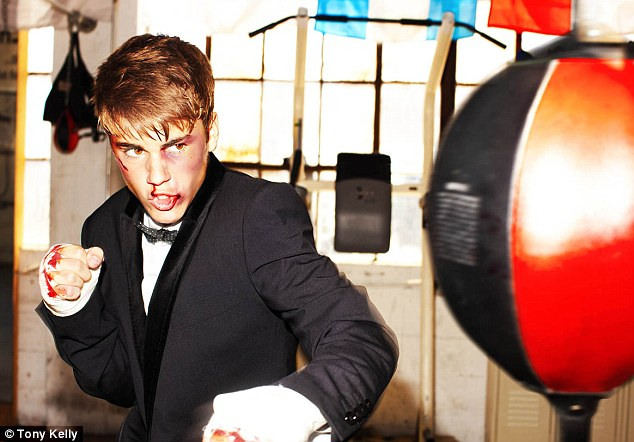Tough guy: In another shot the teen slips on a black tuxedo jacket and goes a few rounds with a speed ball