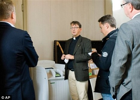 Plastic fantastic: Vicar Johan Tyrberg stands next to a credit card machine in the Carl Gustaf Church in Karlshamn, southern Sweden, to enable worshippers to donate money without having to carry cash