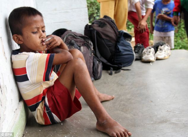 Bad habit: Although his age is shocking to the Western world, it is not such a rare sight in Indonesia and reports state that one in three people smoke in the country
