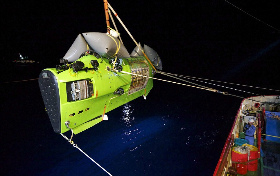 Moment of truth: Deepsea Challenger carrying Carmon is hoisted into the Pacific Ocean on its way to the bottom of the Mariana Trench