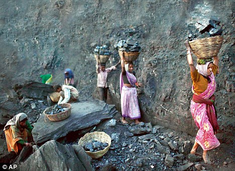 Coalgate: People carry baskets of coal scavenged illegally at an open-cast mine in the village of Bokapahari in the eastern Indian state of Jharkhand