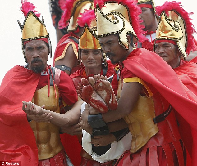 Bloody feet: Filipinos acting as Centurions carry a penitent with bloodied feet after he was nailed to a cross during a reenactment of Jesus Christ's crucifixion on Good Friday in Barangay Cutud, San Fernando, Pampanga in northern Philippines