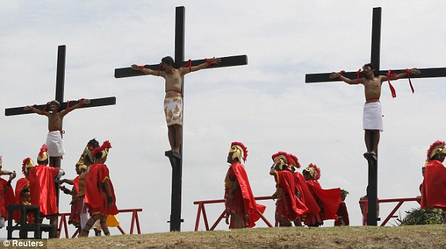 Grim reenactment: Three Filipinos are nailed to crosses in a Good Friday crucifixion in Barangay Cutud, San Fernando. The event attracted a crowd of around 10,000 people