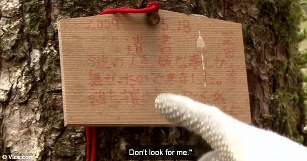 Embittered: Mr Hayano points to a suicide note nailed to a tree in the dense forest known as Jukai