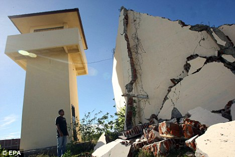 A prison official examines damage to the prison wall that collapsed after the earthquake in Banda Aceh, Indonesia