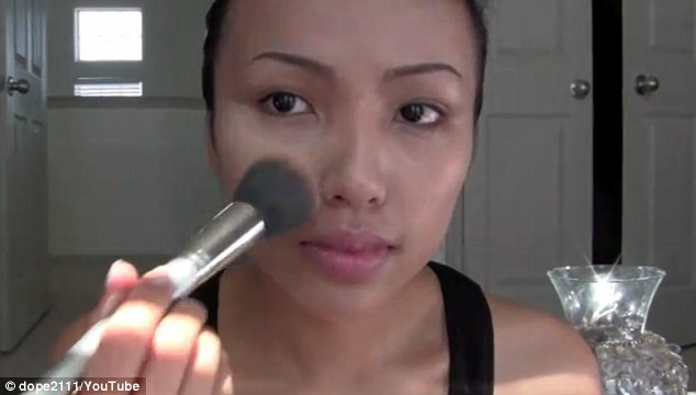 Getting started: Promise brushes on foundation to achieve a flawless complexion at the start of a video in which she mimics Angelina Jolie's make-up looks