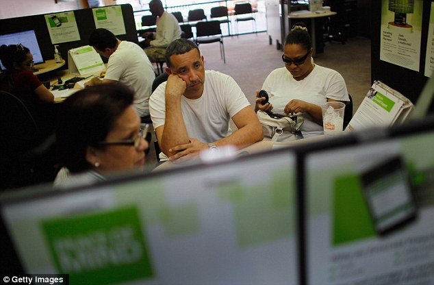 Tuesday blues: Javier Merlo (centre) and his wife Robin Merlo do their taxes at an H&R Block office in Miami, Florida