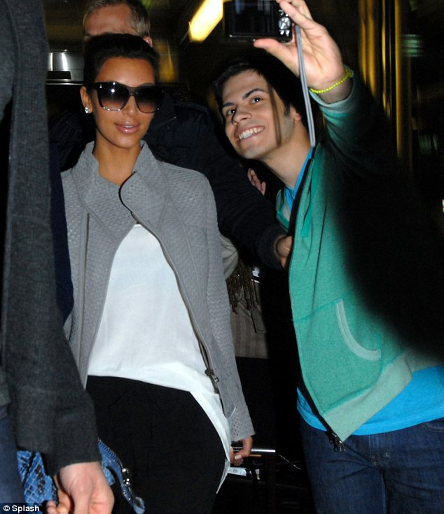 Not in the mood: Kim, 31, didn't appear too pleased to be having a picture with a fan as she arrived in Chicago