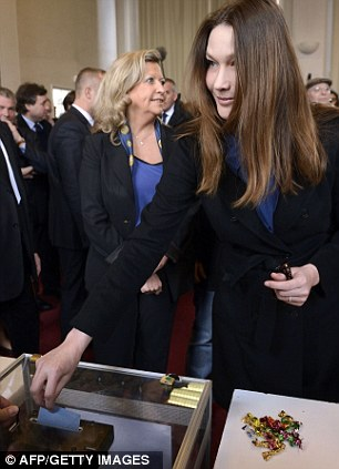 I hope you're going to vote for me darling: France's First Lady Ms Bruni has a final discussion with her husband, left, before casting her vote, right