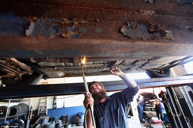 Mechanic Chucky Oliver welds a pipe at his auto repair shop in Owsley County on April 19, 2012 in Booneville, Kentucky