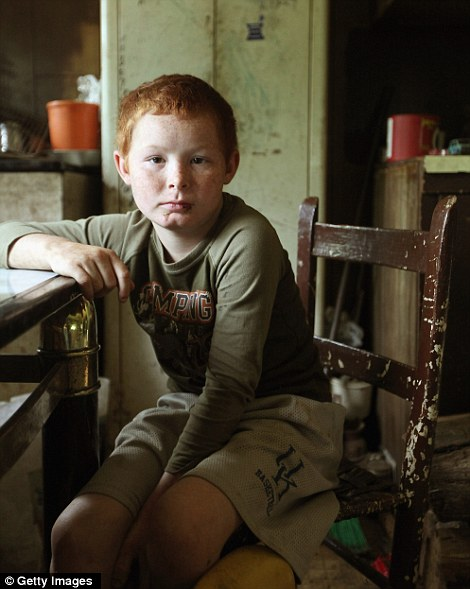 Mose Noble's nephew Johnny Noble, 9, sits in Mose's trailer during a visit on April 21, 2012 in Owsley County, Kentucky