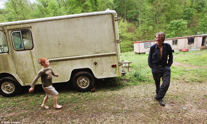 Rural: Nine-year-old Johnny Noble runs barefoot toward his uncle Mose outside the former chimney sweep's trailer in Appalachia