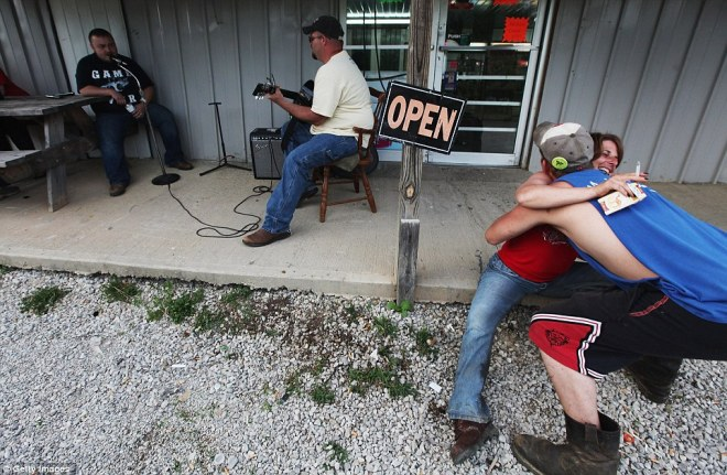 James Moore, centre, plays the guitar as Robert Go, left, sings while revelers hug at Joe's Meat Market #2 in Owsley County