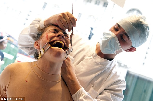 Extreme measures: Jacqueline Traide is restrained and has her mouth clamped open while being subjected to brutal animal testing practices at the Lush store in London's Regent Street today