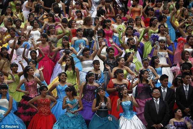 Coming of age: Girls dressed in evening gowns pose for a photograph at the Monument of the Angel of Independence