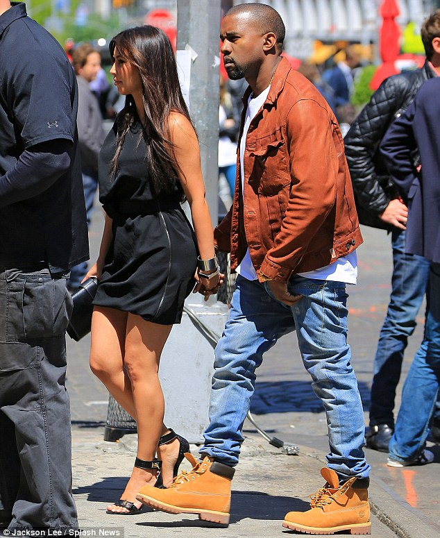 Different fashion memos: The couple held hands as they traipsed the street boasting completely different styles