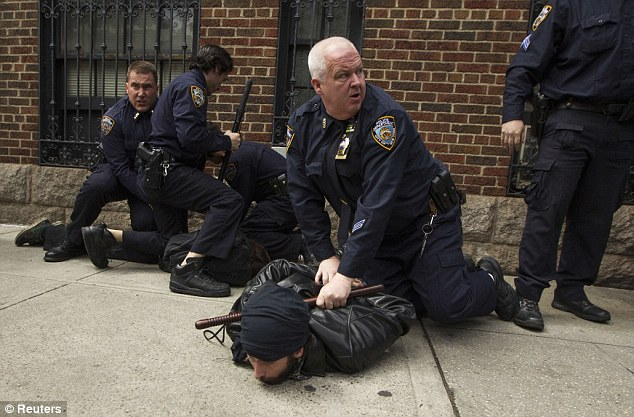 Grounded: NYPD officers use batons to subdue protesters on the sidewalk