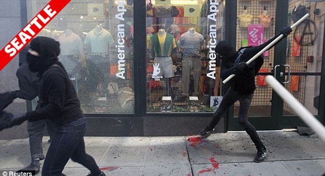 Chaos: Masked protestors use bats and wooden poles to destroy the glass storefront of an American Apparel store in Seattle