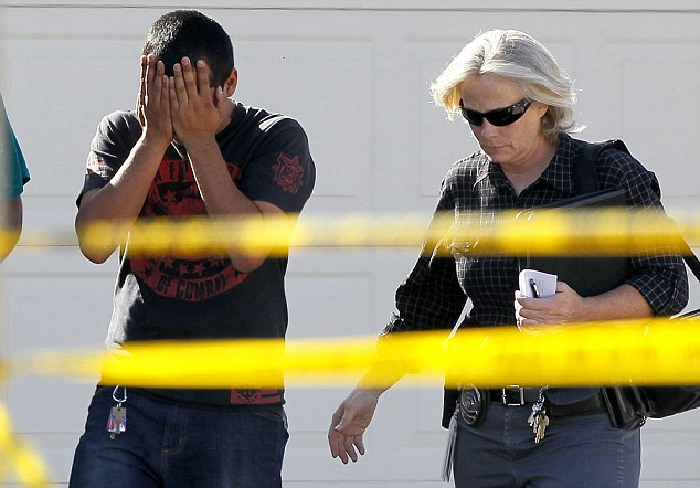 Distraught: A police officer walks with a man who said he had a child inside of the home where five people were shot yesterday