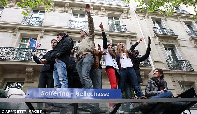 Socialists on top: Elated Hollande supporters climb on a bus stop in Paris