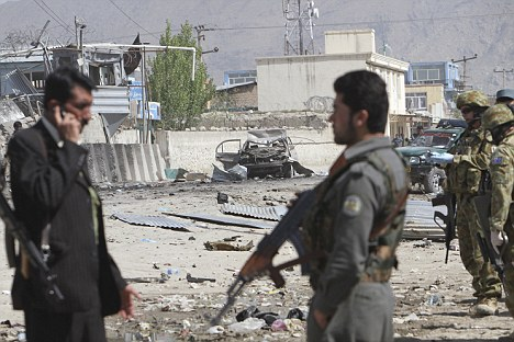 Unrest: Afghan security personnel and NATO soldiers stand at the scene of suicide car bombing and Taliban militants' attack in Kabul on a compound housing hundreds of foreigners in the Afghan capital on May 2