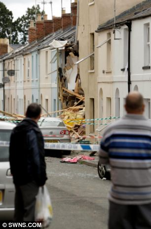 Remains: Neighbours survey the scene of the blast which remains behind police tape