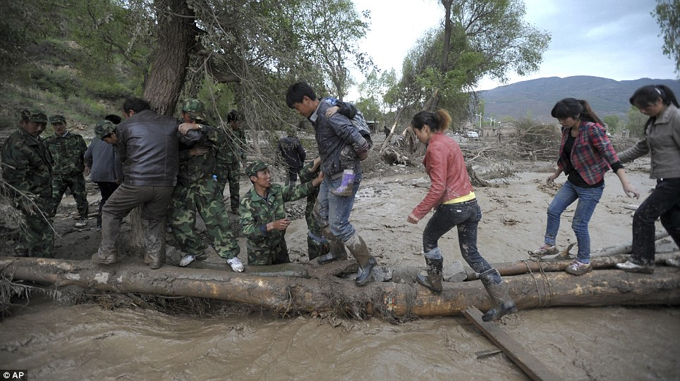 Mudflow: Soldiers help people to evacuate in Goumen Village, Minxian County, in northwest China's Gansu Province, after heavy rain and hail prompted a massive mudslide that killed at least 44 people