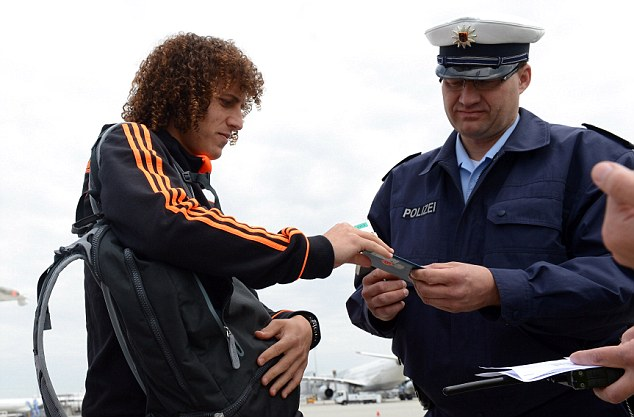 I recognise the hair, sir: David Luiz has his passport checked by police at the airport