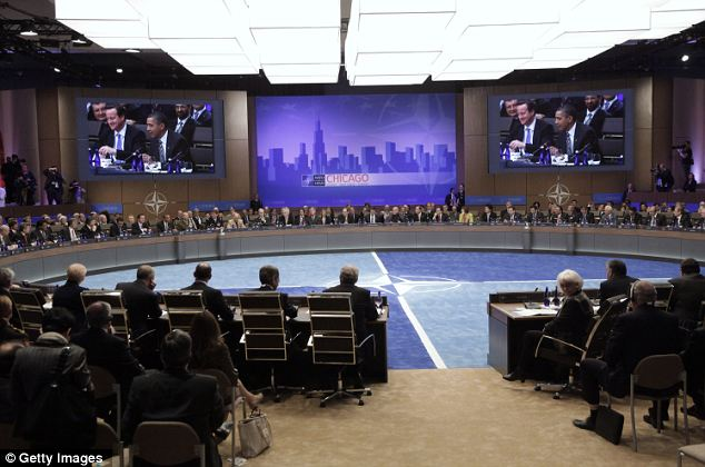 Round table: Mr Obama is seen speaking on-screen at the meeting yesterday which was designed to set out a final timetable for the handover to Afghan security forces, which will lead all combat operations by mid-2013