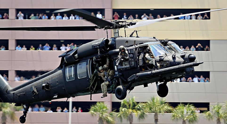 Don't shoot! Spectators watch with cameras as a demonstration by special operations troops on an Army MH-60 Blackhawk near the Tampa Convention Center draws crowds yesterday