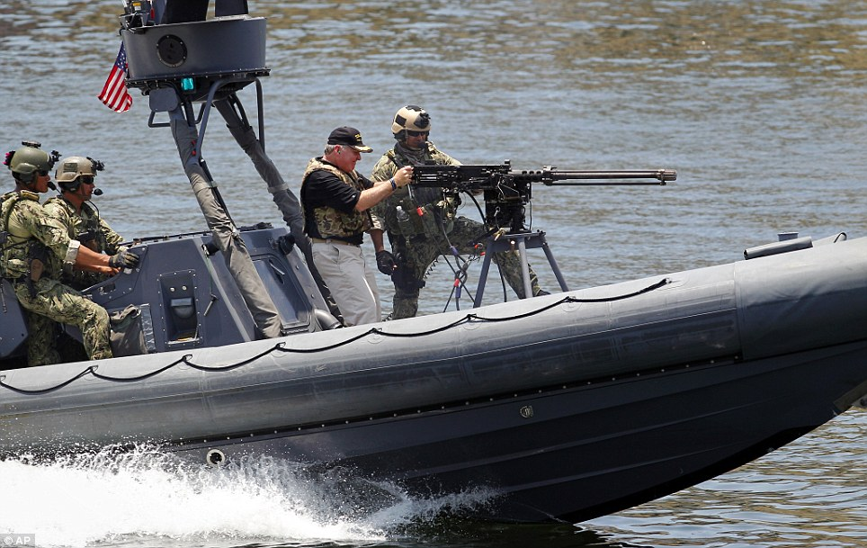 Tampa Mayor Bob Buckhorn fires blank rounds from a machine gun mounted to a rigid hull inflatable boat