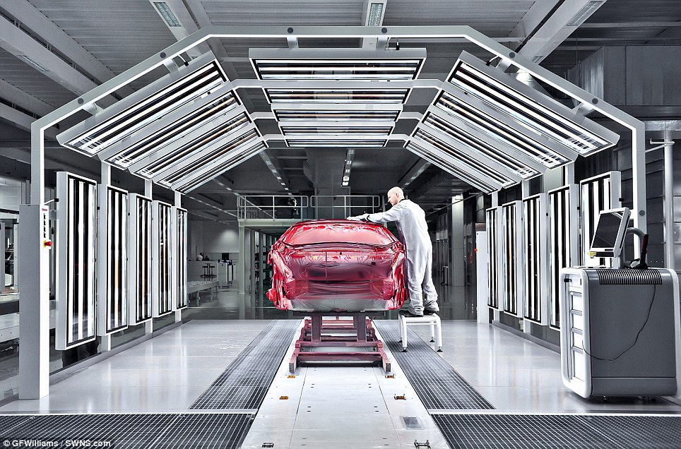A worker inspects one of the vehicles - kept under wraps as it goes through the finishing stages