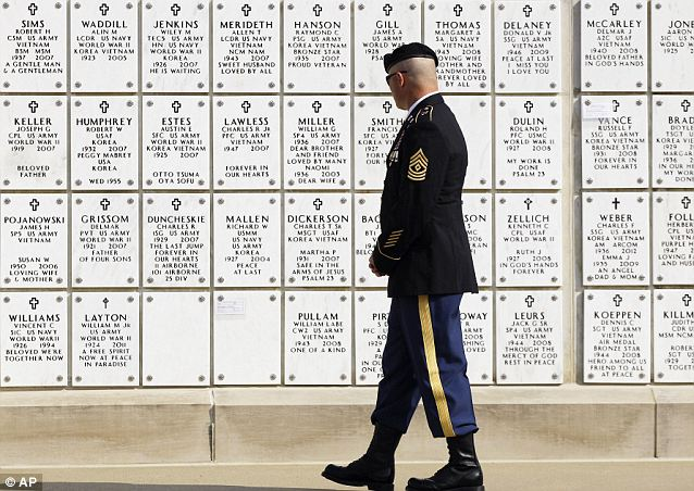 Reflection: First Sgt. Christopher Pry reads the names on crypts at the Kentucky Veterans Cemetery West on Friday in Hopkinsville, Kentucky