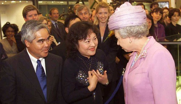 Britain's Queen Elizabeth II, right, with Associated Press photographer Nick Ut, left and Phan Thi Kim Phuc, center in London in 2000