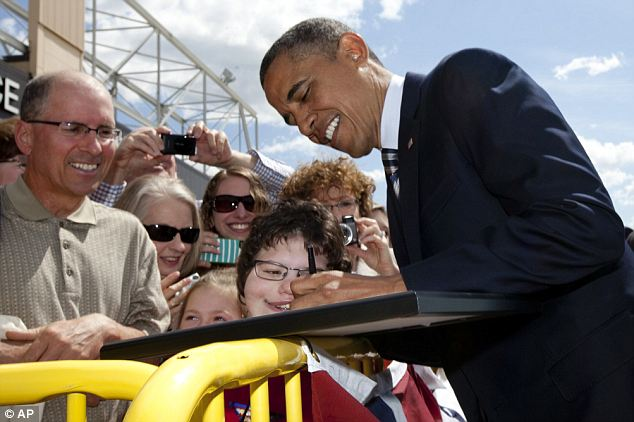 Despite the bad numbers Obama was all smiles after arriving at Minneapolis-St. Paul International as he signed a framed photograph of himself