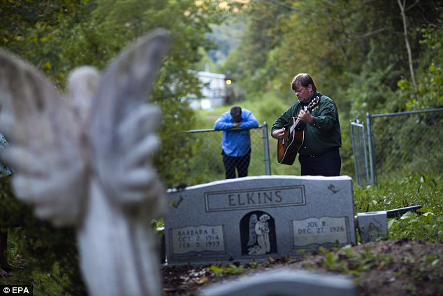 David Payne sings at the gravesite of Bob Elkins, the former coal miner who founded the Jolo church 50 years ago