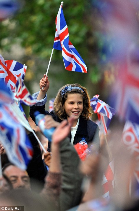 A girl waves a Union Flag as the crowds congregate along The Mall for the concert